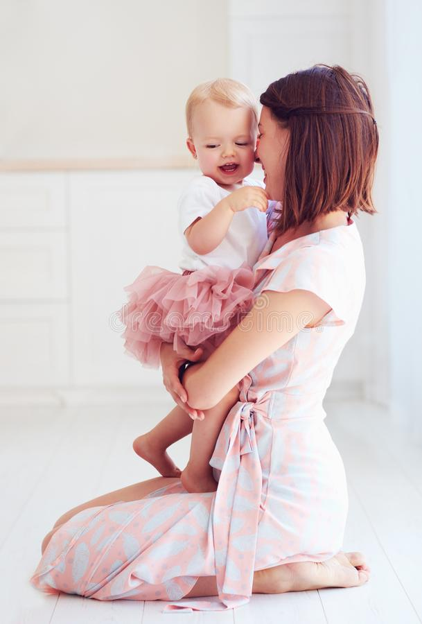Glückliche Mutter, die zu Hause ihr kleines Baby umarmt stockbilder