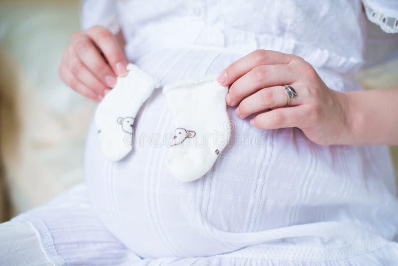 Glückliche Mutter in Erwartung der Geburt ihres Babys Schwangere Frau, die gestrickte weiße Socken auf Bauchhintergrund hält Naha stockfoto