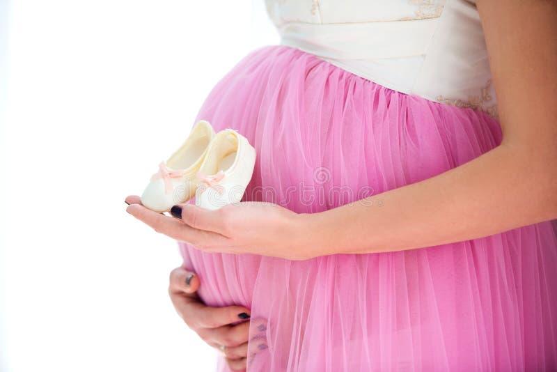 Glückliche Mutter in Erwartung der Geburt der Tochter Holdingbaby-Beutenturnschuhe der schwangeren Frau auf Bauchhintergrund Naha lizenzfreies stockbild