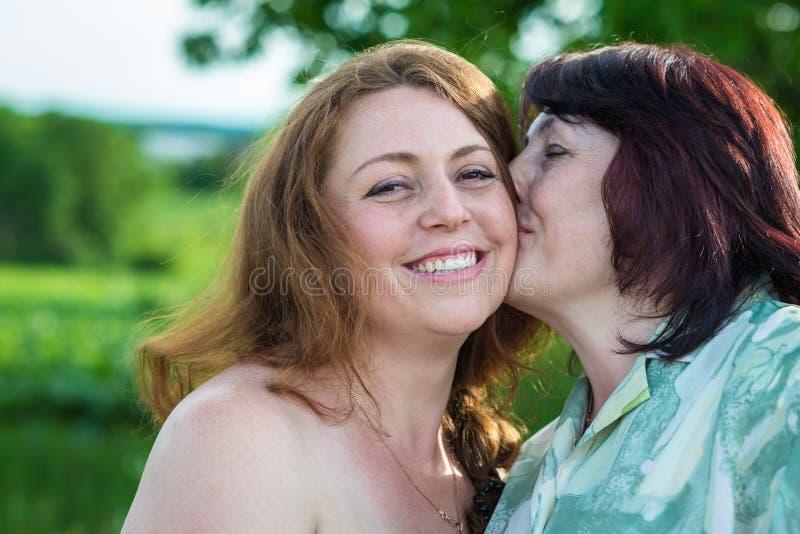 Glückliche Mutter küsst Tochter stockfoto