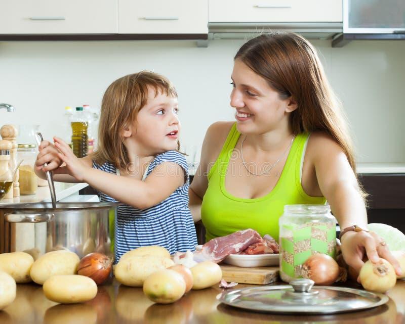 Glückliche Mutter mit dem Kind, das Suppe f kocht stockbilder