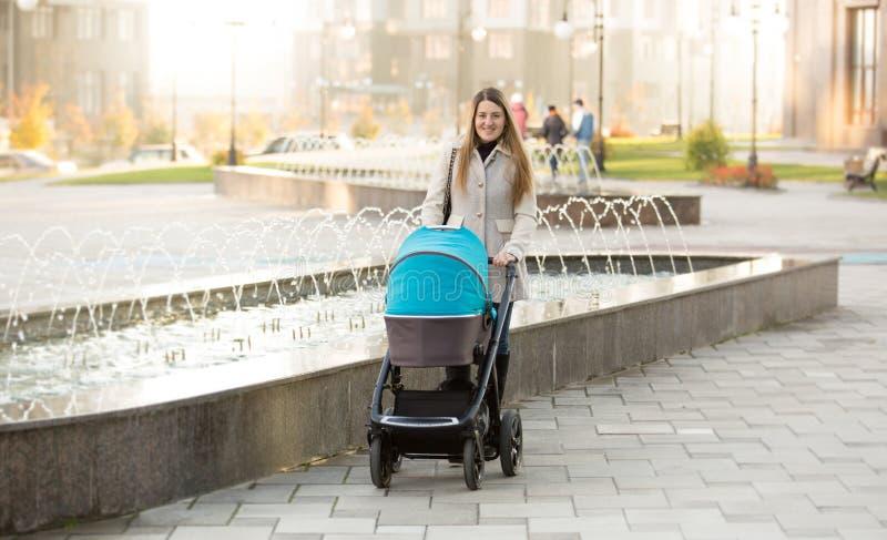 Glückliche Mutter mit dem Kinderwagen, der auf Straße nahe Brunnen geht stockfotografie
