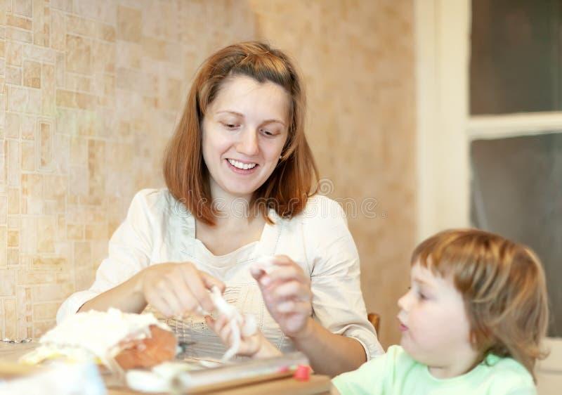 Glückliche Mutter mit der Tochter, die in der Folie kocht lizenzfreie stockfotografie