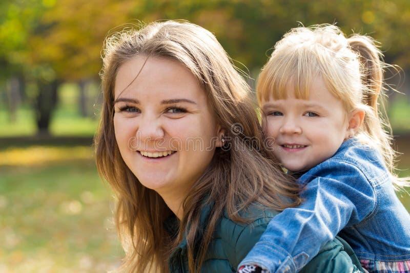 Glückliche Mutter mit einem Lächeln, das mit ihrer Tochter im Park an einem Sommertag spielt lizenzfreie stockfotografie