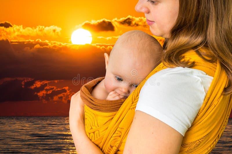 Glückliche Mutter mit ihrem Baby in einem Riemen lizenzfreies stockfoto