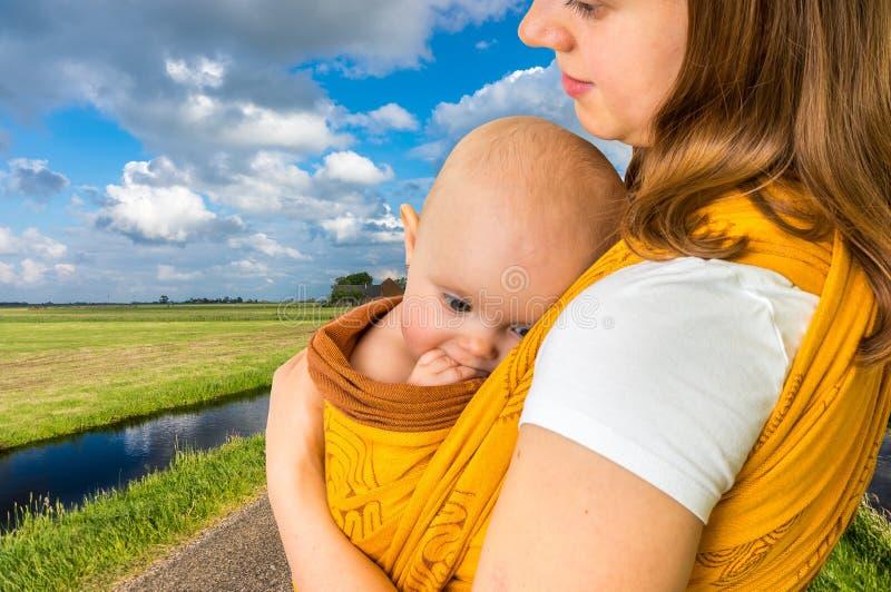 Glückliche Mutter mit ihrem Baby in einem Riemen stockfotos