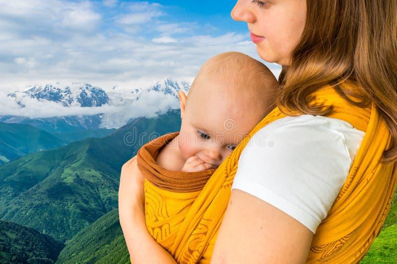 Glückliche Mutter mit ihrem Baby in einem Riemen lizenzfreie stockfotos