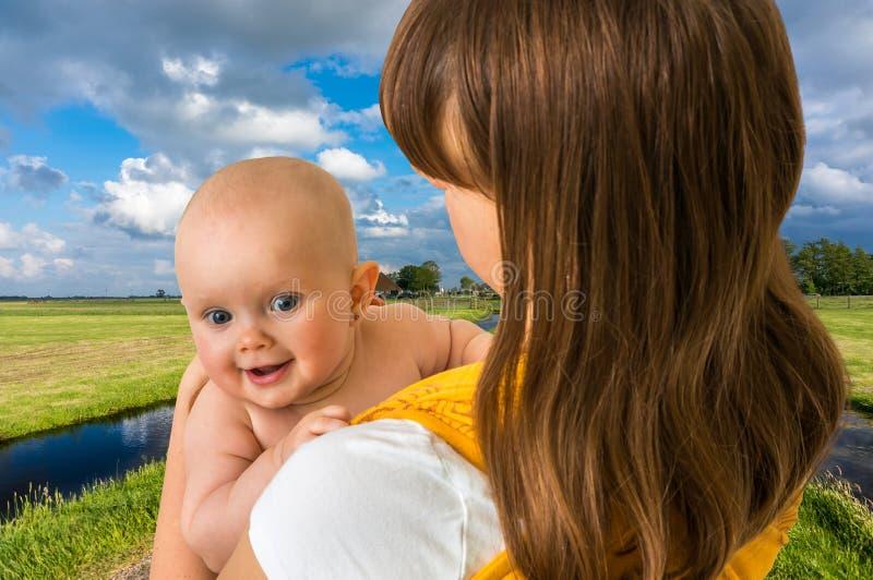 Glückliche Mutter mit ihrem Baby in einem Riemen stockbild