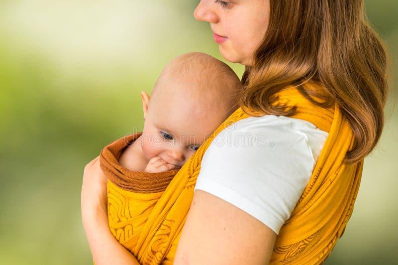 Glückliche Mutter mit ihrem Baby in einem Riemen - auf Grün lizenzfreie stockbilder
