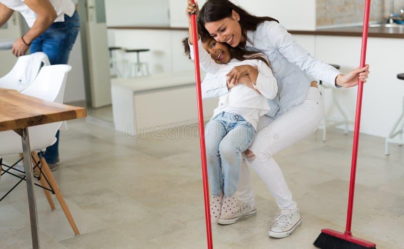 Glückliche Mutter mit ihrem Kinderreinigungshaus stockfotografie