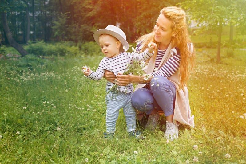 Glückliche Mutter mit ihrem kleinen Sohn in einem großen Hut gehen auf eine grüne Wiese in einem Sommerpark mit einem Blumenstrau stockbild