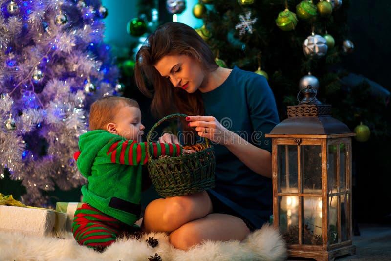 Glückliche Mutter mit ihrem kleinen Sohnblick auf Weihnachtsgeschenke im Docht stockbild