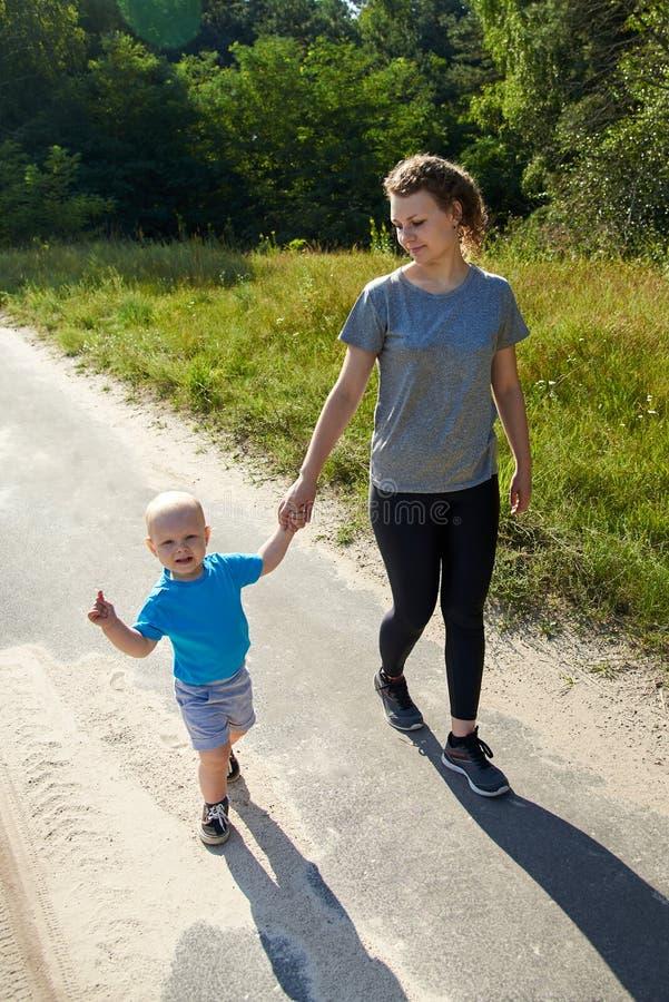 Glückliche Mutter mit ihren Sohnwegen auf einer Asphaltstraße in der Natur an einem Sommertag stockbilder