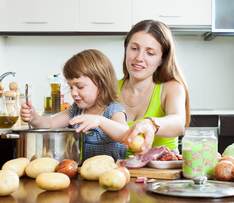 Glückliche Mutter mit Kinderdem kochen stockfotos