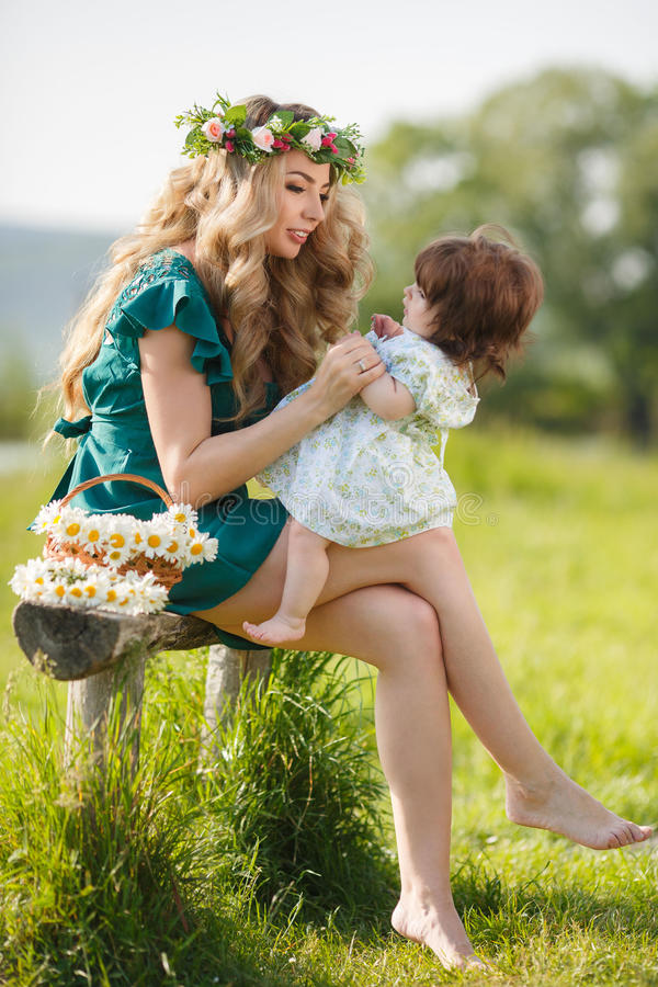 Glückliche Mutter mit kleiner Tochter auf der Wiese stockbilder
