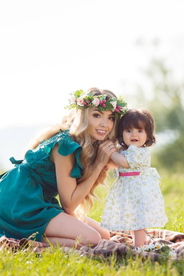 Glückliche Mutter mit kleiner Tochter auf der Wiese lizenzfreie stockbilder