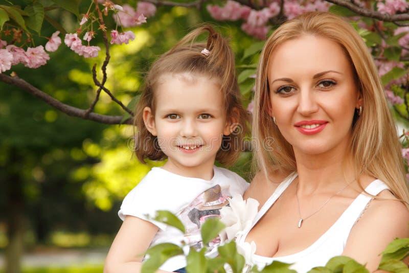 Glückliche Mutter mit kleiner Tochter leckt Süßigkeit lizenzfreies stockbild