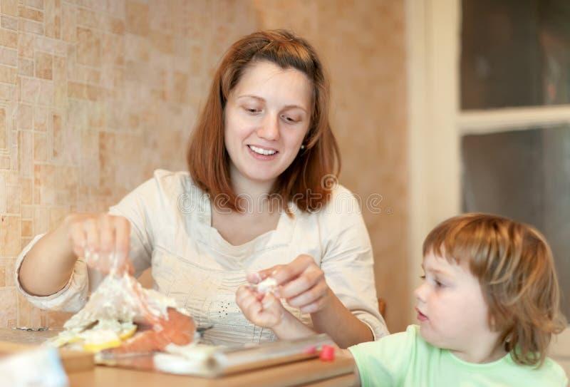 Glückliche Mutter mit Mädchen cookis in der Küche lizenzfreies stockfoto