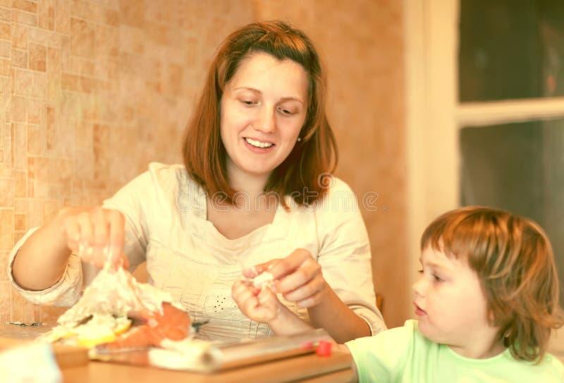 Glückliche Mutter mit Mädchen cookis in der Küche stockbilder