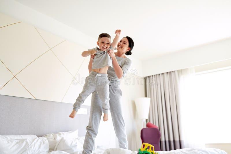 Glückliche Mutter mit Sohn im Bett zu Hause oder im Hotelzimmer lizenzfreie stockfotos