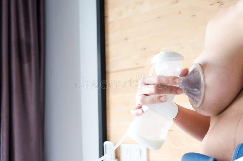 Glückliche Mutter pumpt Muttermilch von der Brust für neugeborenes Baby stockfotografie