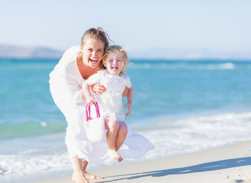 Glückliche Mutter und Baby auf dem Seeufer, das Spaß hat stockfoto