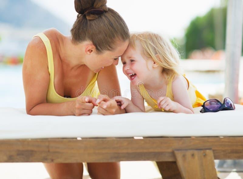Glückliche Mutter und Baby, die am Poolside spielt lizenzfreie stockbilder