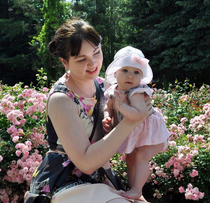 Glückliche Mutter und Baby unter Rosen lizenzfreies stockfoto
