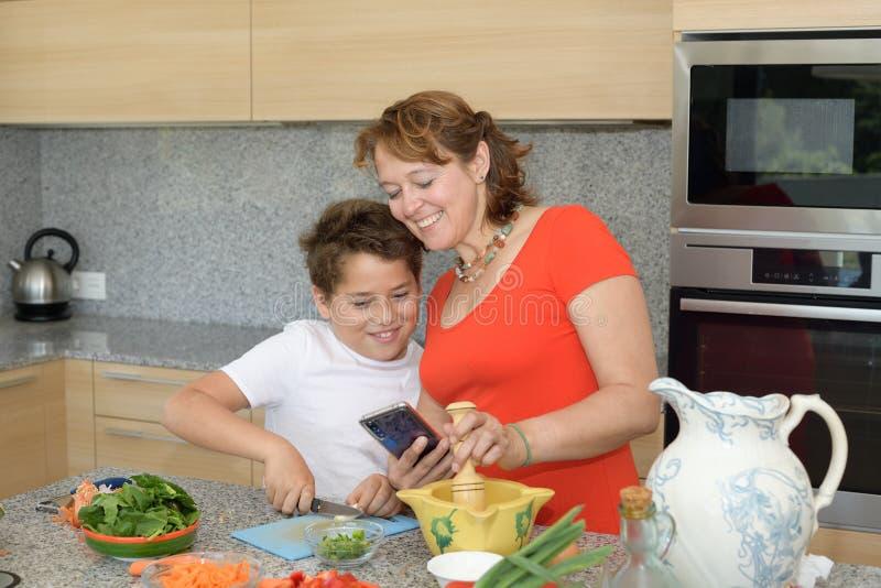 Glückliche Mutter und der Sohn, die Mittagessenwann vorbereitet, konsultiert ein Rezept stockfoto