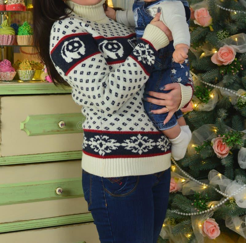 Glückliche Mutter und entzückendes Baby, die Flitter gegen inländischen festlichen Hintergrund mit Weihnachtsbaum hält lizenzfreie stockfotografie