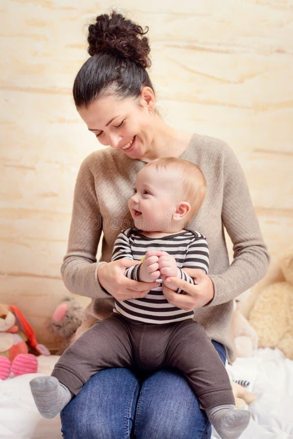 Glückliche Mutter und ihr Baby, die an der Kamera lächelt stockbild