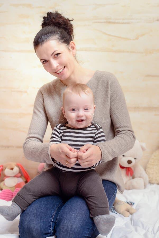 Glückliche Mutter und ihr Baby, die an der Kamera lächelt stockfotos
