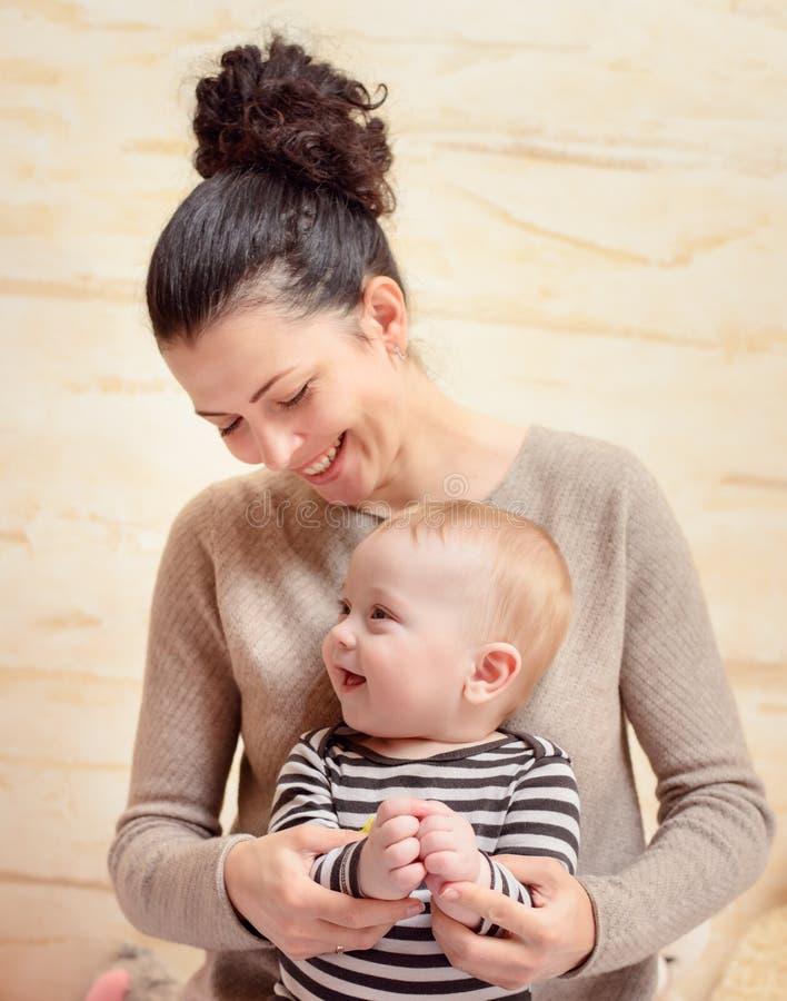 Glückliche Mutter und ihr Baby, die an der Kamera lächelt lizenzfreies stockbild