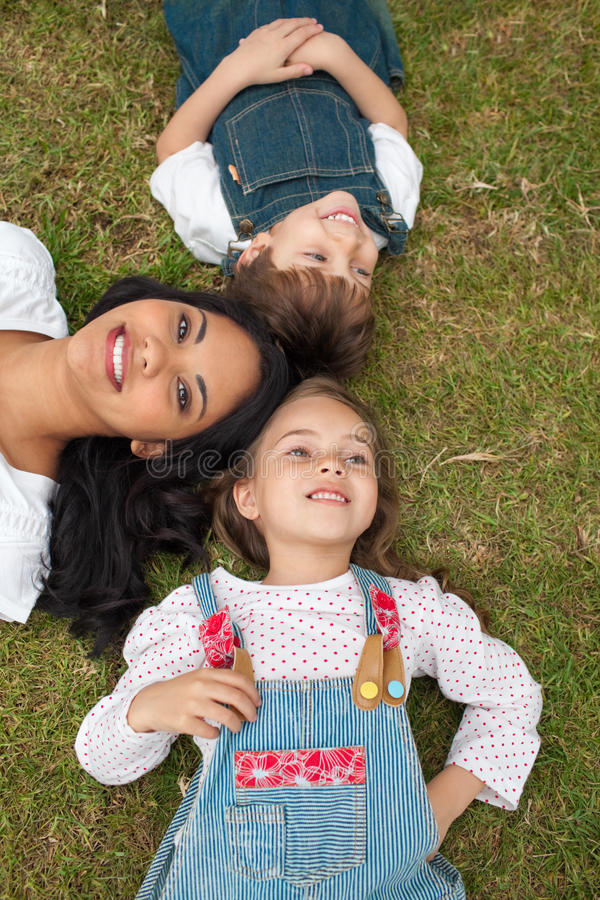 Glückliche Mutter und ihre Kinder, die auf dem Gras liegen stockfoto