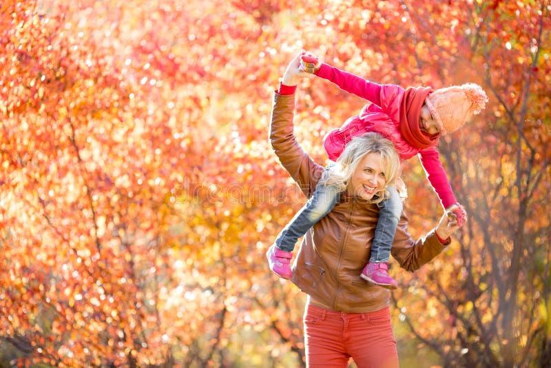 Glückliche Mutter und Kind, die den Spaß zusammen im Freien im Herbst hat lizenzfreie stockfotografie