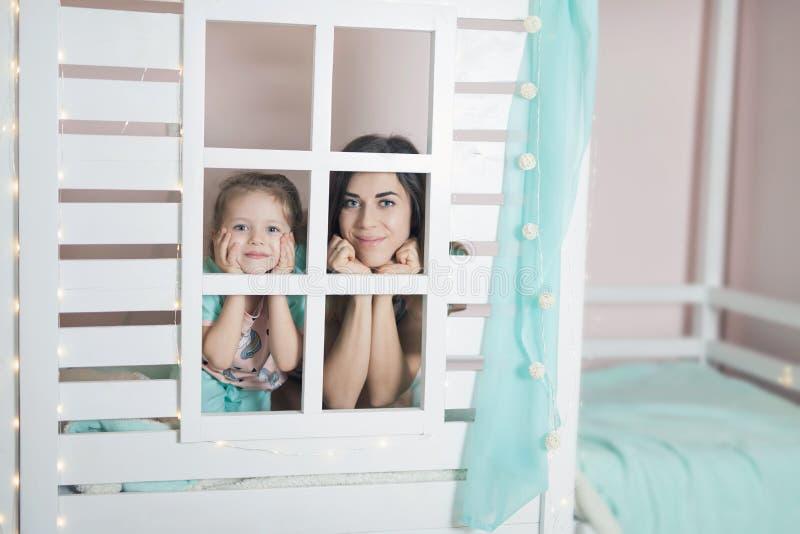 Glückliche Mutter und Kind, die für Schlaf im Kinderhaus sich vorbereitet stockfotografie