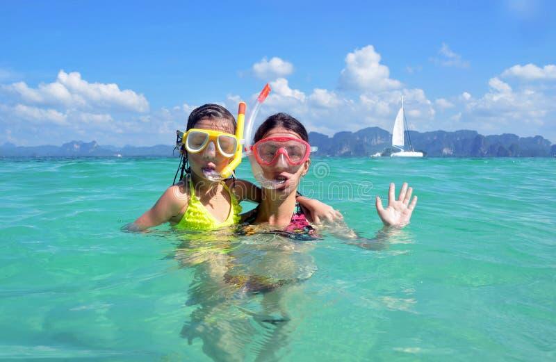 Glückliche Mutter und Kind, die im tropischen Meer schnorchelt stockfotografie