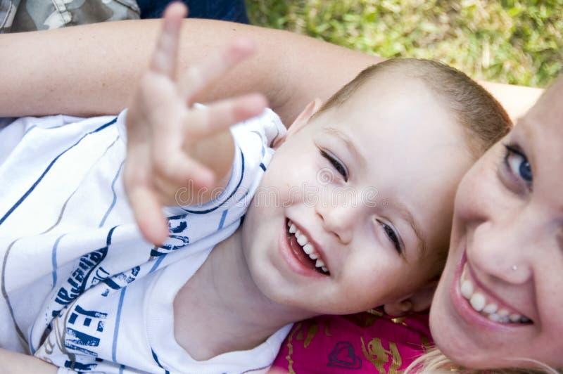 Glückliche Mutter und Kind, die in Richtung zur Kamera aufwirft lizenzfreies stockfoto
