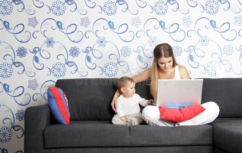 Glückliche Mutter und Kind mit Laptop zu Hause lizenzfreie stockbilder