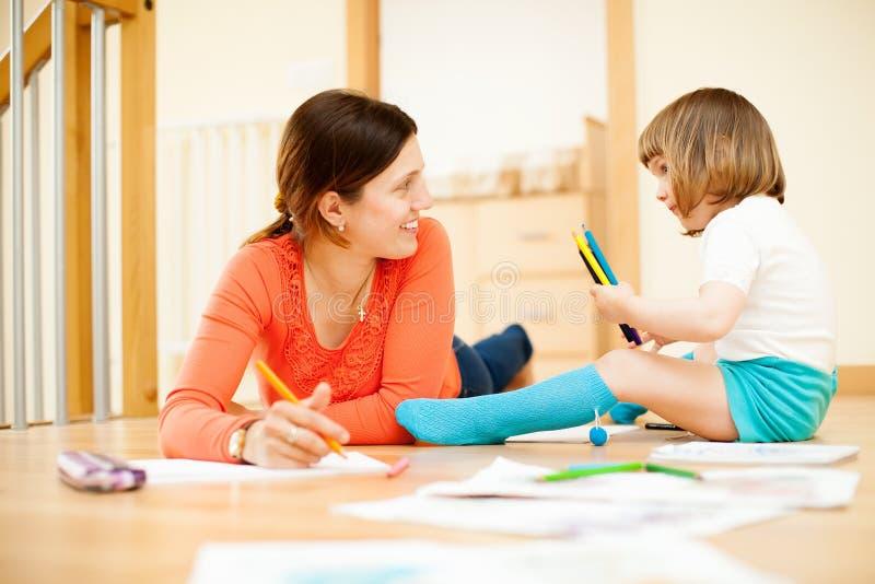 Glückliche Mutter- und Kinderzeichnung am Boden stockbild