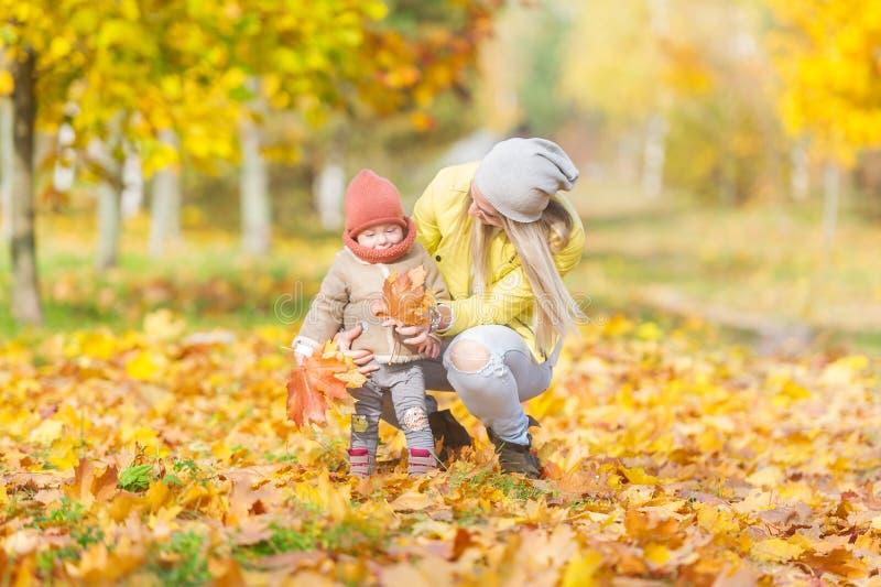 Glückliche Mutter und kleine Tochter, die zusammen Spaß im Herbstpark spielt stockfoto