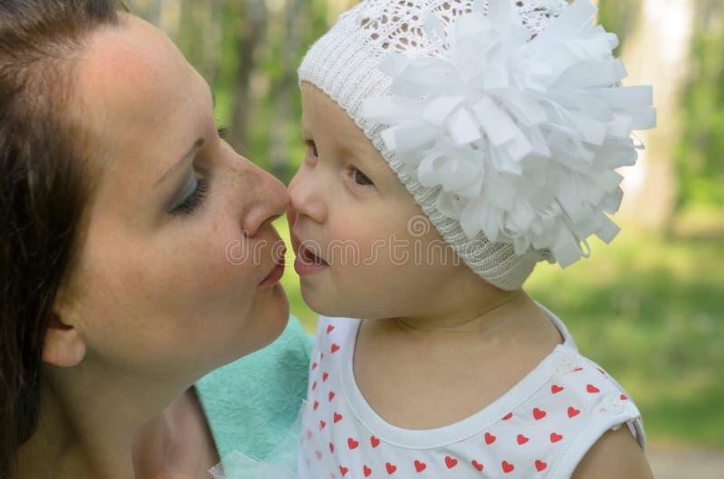 Glückliche Mutter und kleine Tochter im Park stockfotos