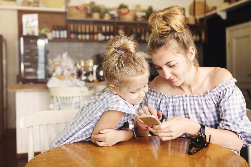 Glückliche Mutter und kleines Mädchen, die zu Abend isst und Smartphone verwendet lizenzfreies stockbild