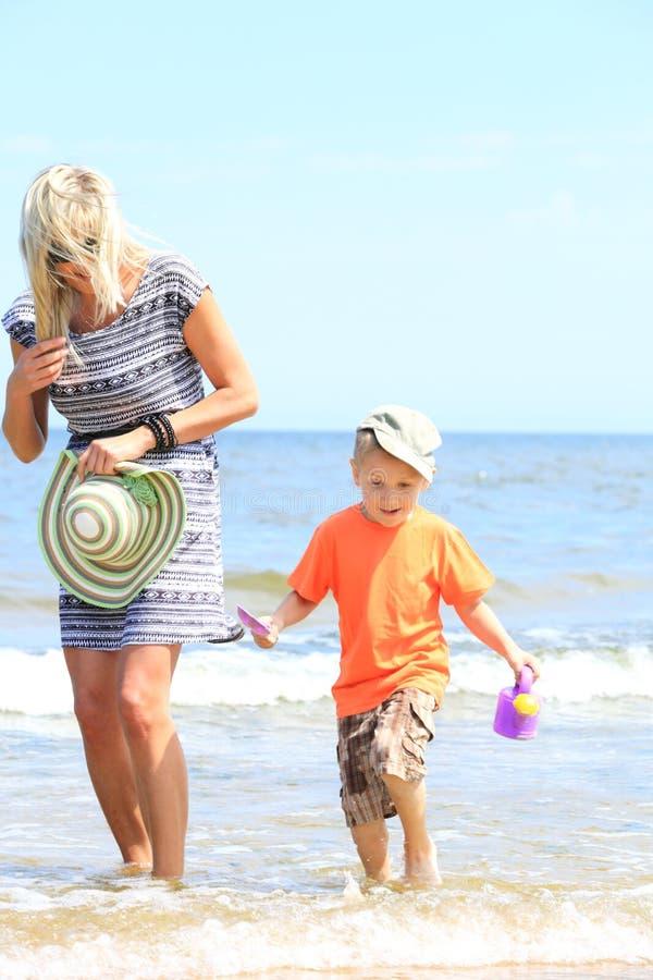 Glückliche Mutter und Sohn, die auf Strand spielt stockfotos