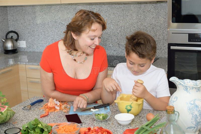 Glückliche Mutter und Sohn, die das Mittagessen mit einem Mörser vorbereitet stockfoto