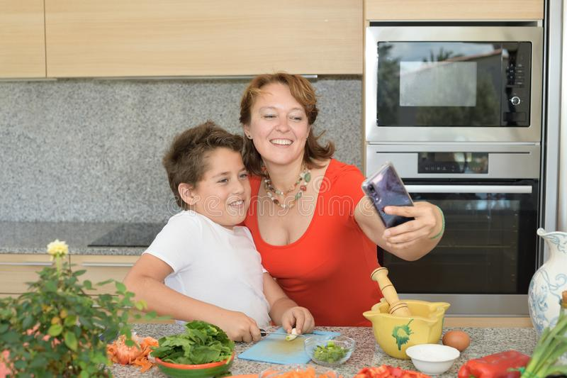 Glückliche Mutter und Sohn, die das Mittagessen vorbereitet, während ein 'selfie nehmen Sie stockfotos
