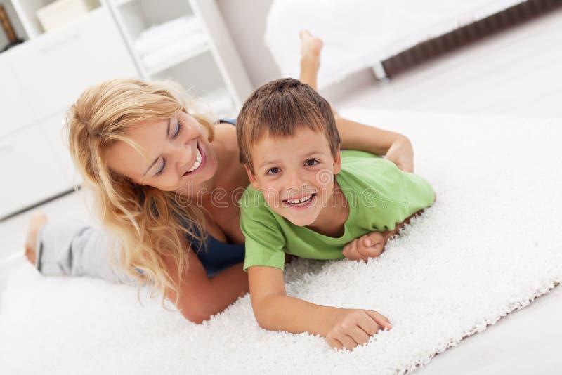Glückliche Mutter und Sohn, die im Wohnzimmer spielt lizenzfreies stockbild