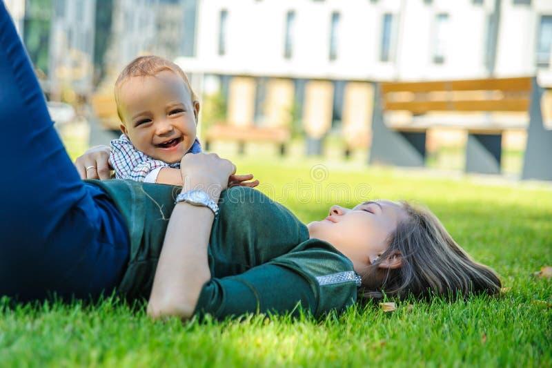 glückliche Mutter und Sohn liegen auf dem Gras im Park lizenzfreies stockbild