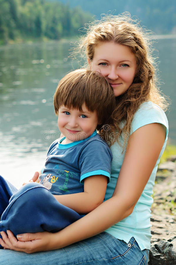 Glückliche Mutter und Sohn nahe dem Fluss stockbild