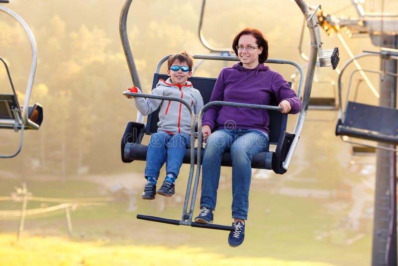 Glückliche Mutter- und Sohnfahrsesselbahn stockfotos